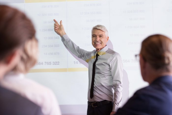 Smiling senior businessman pointing to table on projection screen while explaining ideas to audience seen partly