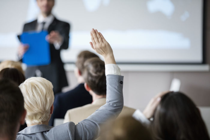 Rear view of businesswoman raising hand during seminar